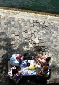 A beautiful day beckoned these people to pack a picnic lunch and enjoy a peaceful outing along the Seine River.